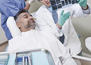 Dentist Explaining Mature Patient X-Ray